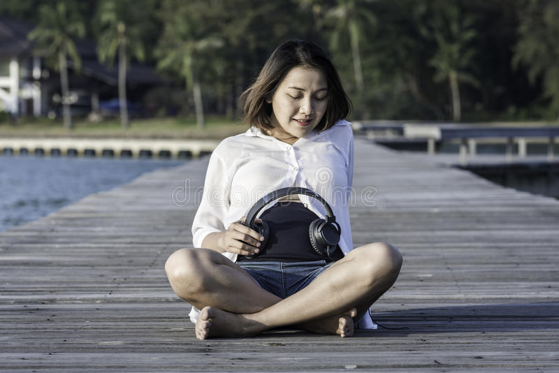 Mulher gravida bonita que guarda fones de ouvido fotos de stock royalty free