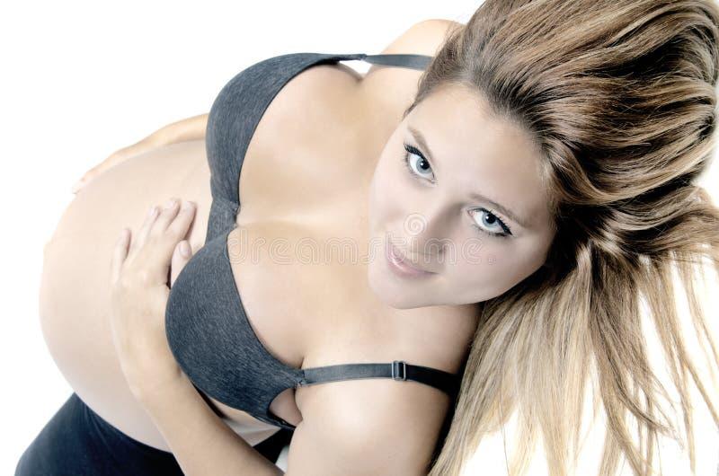 Mulher gravida bonita que olha a câmera e que sorri quando lyi foto de stock royalty free