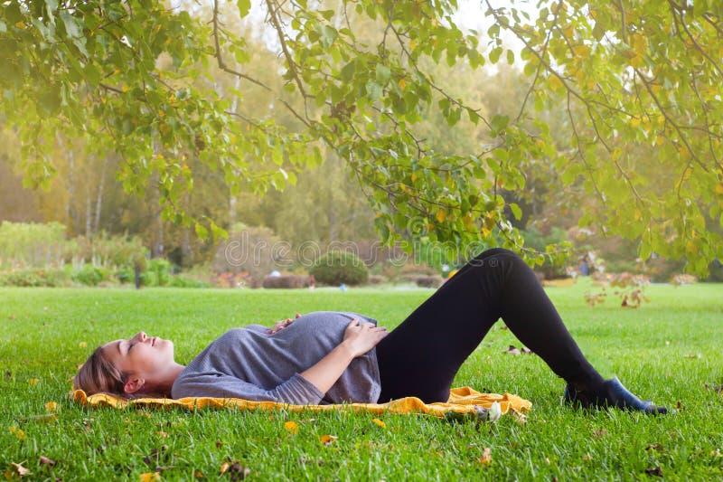 Mulher gravida bonita que relaxa na grama imagens de stock royalty free