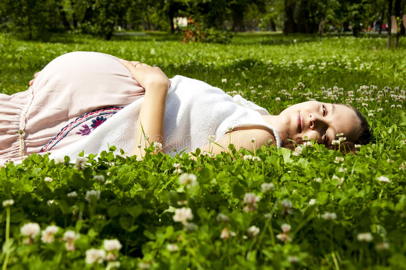 Mulher gravida bonita que relaxa na grama fotografia de stock royalty free