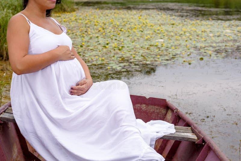 Mulher gravida bonita que relaxa no barco no rio fotografia de stock