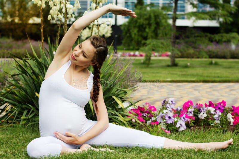 Mulher gravida bonita que relaxa no parque imagem de stock