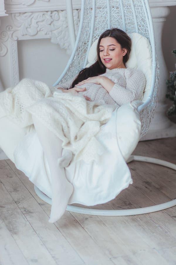 A mulher gravida bonita que senta-se no casulo de vime preside em casa foto de stock royalty free