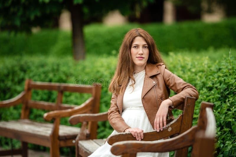 Mulher gravida bonita que senta-se no parque no banco fotografia de stock royalty free