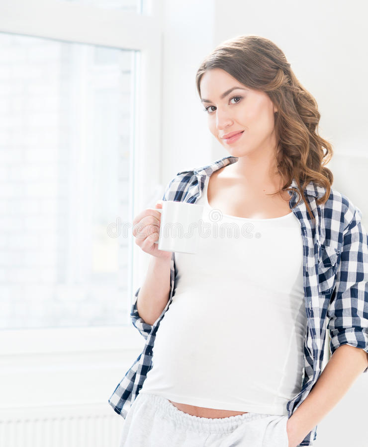 Mulher gravida bonita que tem uma xícara de café fotografia de stock royalty free