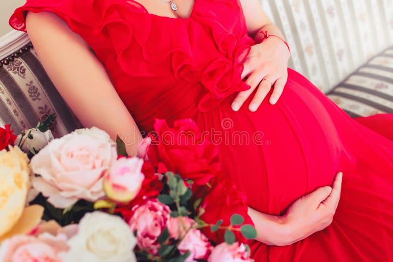 Mulher gravida bonita que toca em sua barriga com mãos na sala de visitas imagem de stock royalty free