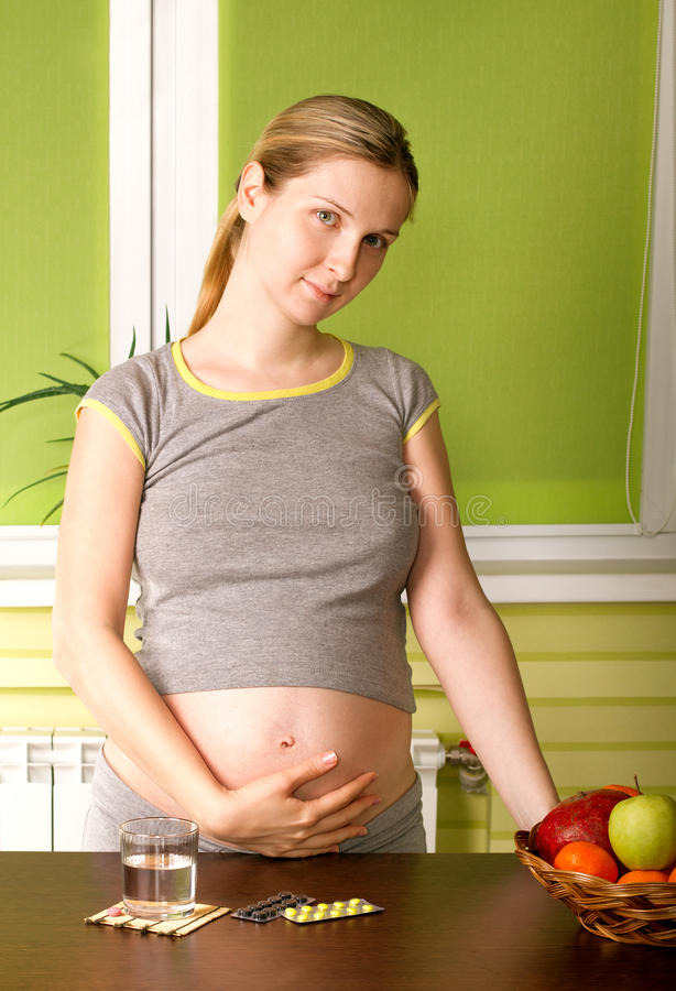 Mulher gravida bonito na cozinha foto de stock royalty free