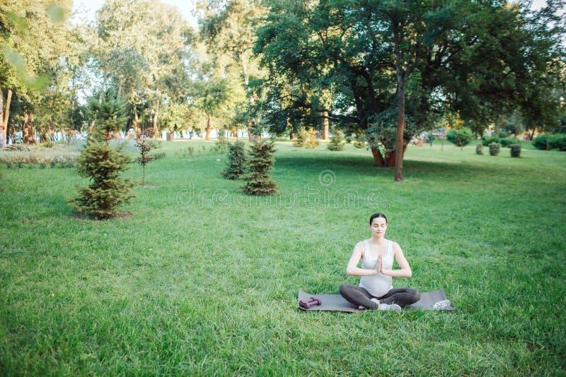 A mulher gravida calma e calma senta-se na pose dos lótus no parque fora apenas Guarda as mãos junto reza dentro a posição foto de stock royalty free