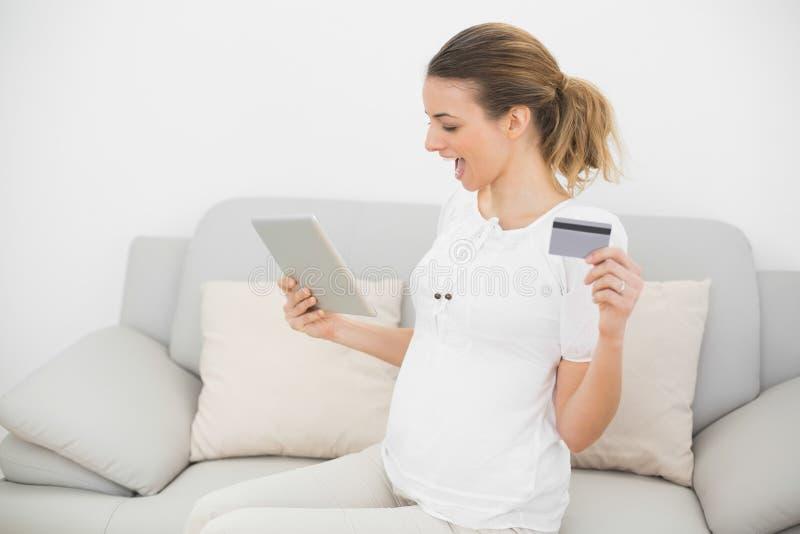 Mulher gravida cheering bonito que usa sua tabuleta para compras ao domicílio fotografia de stock royalty free