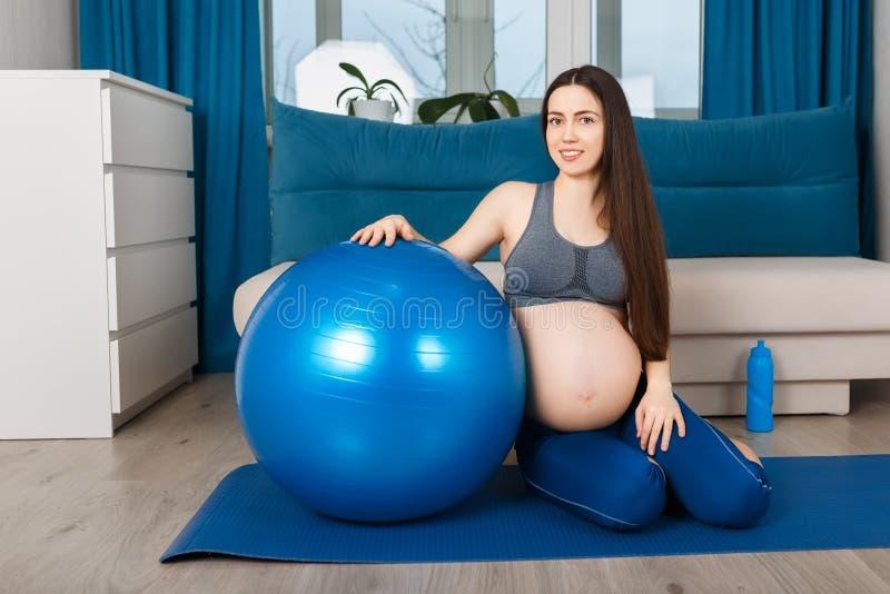 Mulher gravida com bola do ajuste em casa fotos de stock royalty free