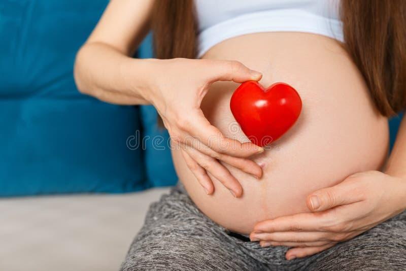 Mulher gravida com coração na barriga fotografia de stock royalty free