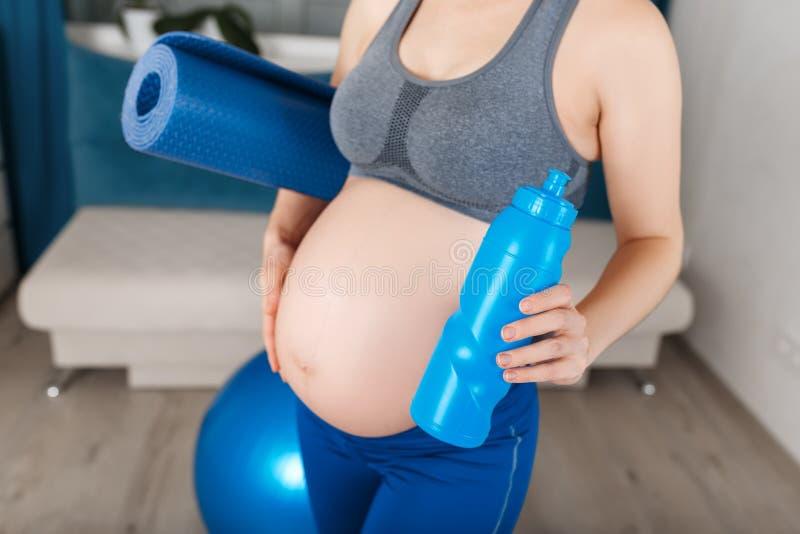 Mulher gravida com esteira da ioga e garrafa da água fotos de stock royalty free