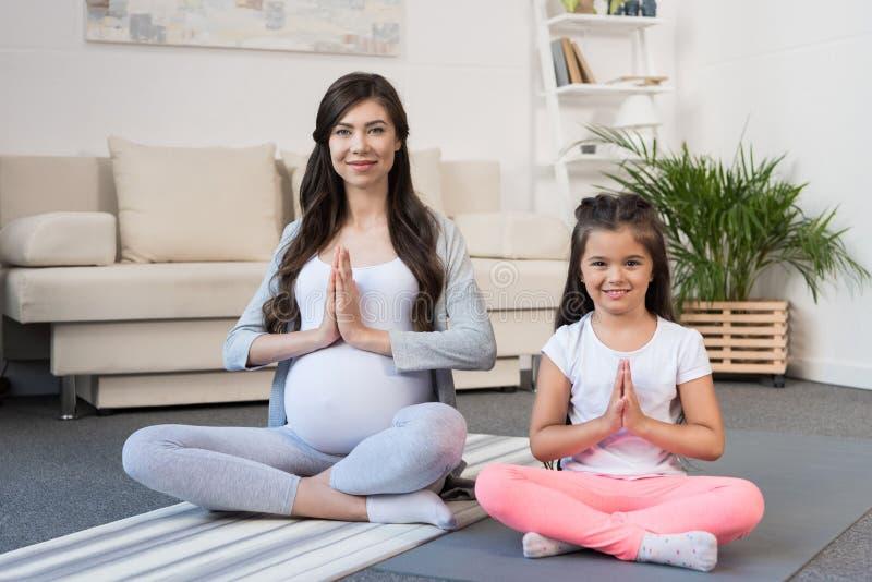 Mulher gravida com a filha na pose dos lótus fotografia de stock