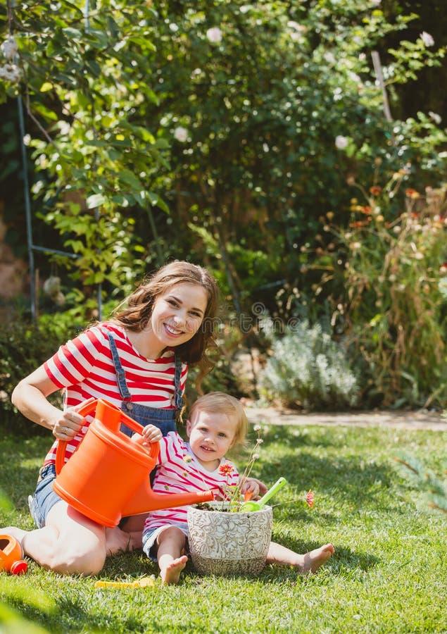 Mulher gravida com a filha pequena no jardim fotografia de stock royalty free