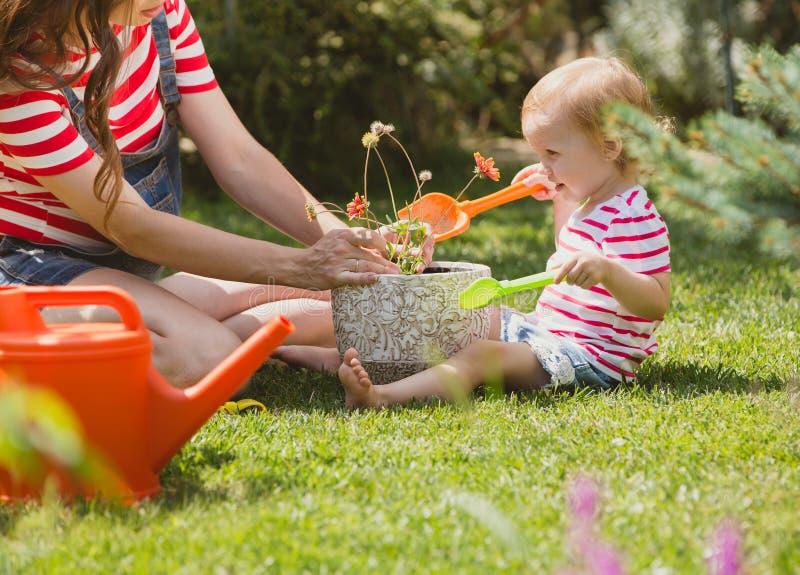 Mulher gravida com a filha pequena no jardim imagens de stock royalty free