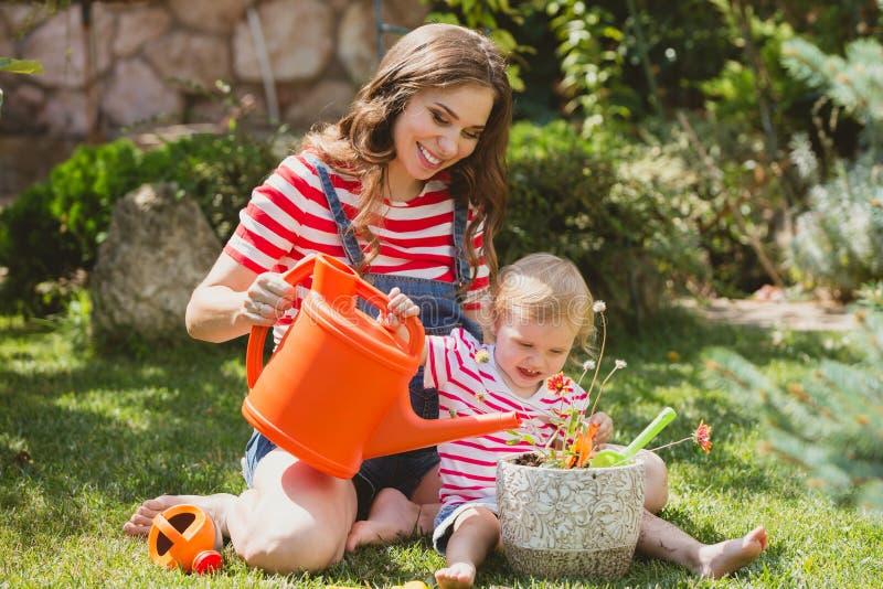Mulher gravida com a filha pequena no jardim fotos de stock