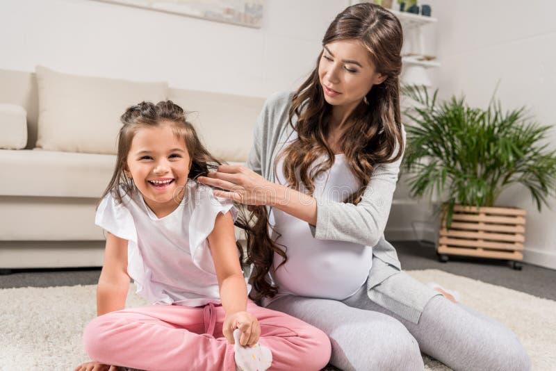 Mulher gravida com a filha que senta-se no tapete imagem de stock royalty free