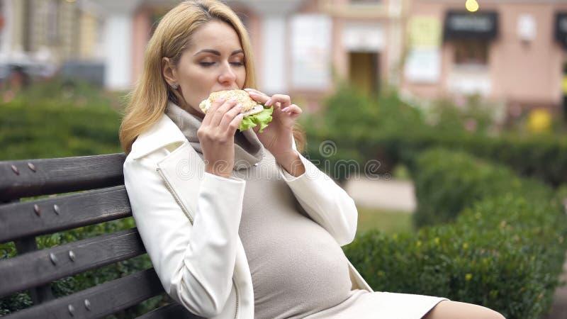 Mulher gravida com fome que aprecia o hamburguer delicioso que senta-se no banco no parque imagens de stock