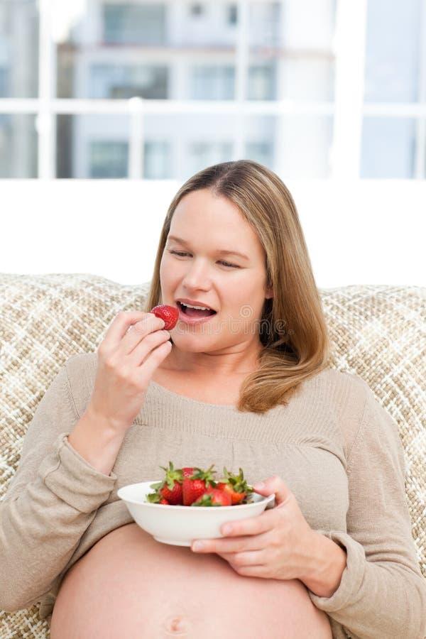 Mulher gravida com fome que come morangos fotografia de stock royalty free