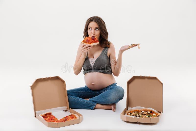 Mulher gravida com fome que come a pizza fotografia de stock