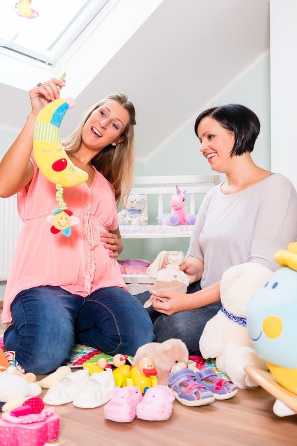Mulher gravida com o amigo na sala em perspectiva do bebê imagem de stock royalty free