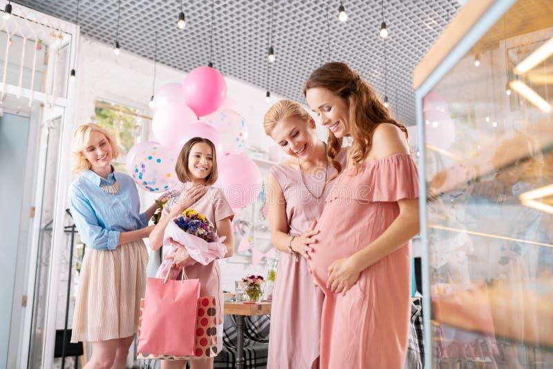 Mulher gravida com o cabelo ondulado que sente a escuta feliz cumprimentos foto de stock royalty free