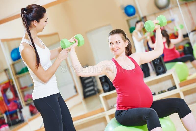 Mulher gravida com o instrutor que faz o exercício da bola da aptidão fotografia de stock royalty free