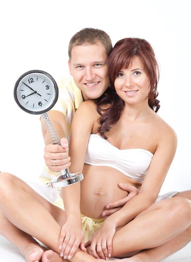 Mulher gravida com o marido, prendendo um pulso de disparo foto de stock