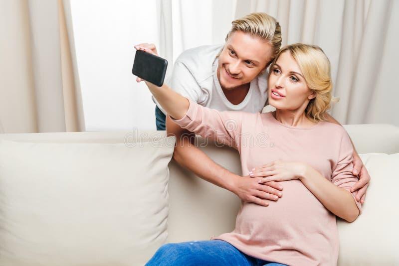 Mulher gravida com o marido que toma o selfie com smartphone em casa imagens de stock royalty free