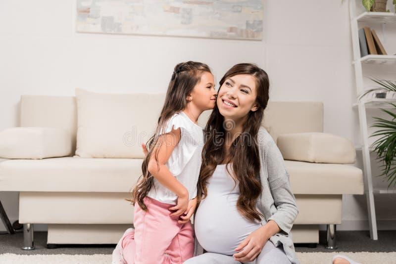 Mulher gravida com o mordente de beijo da filha imagem de stock royalty free