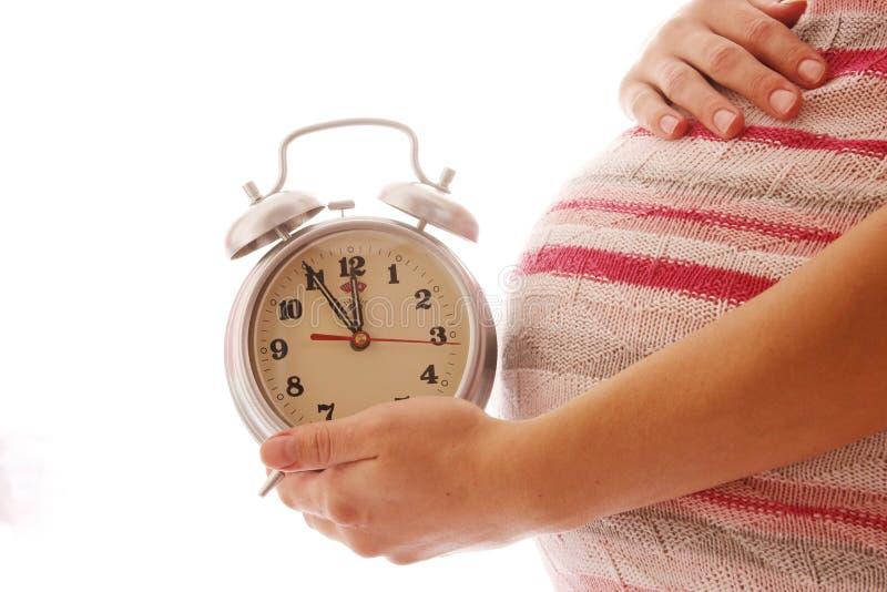 Mulher gravida com pulso de disparo em um fundo branco imagens de stock