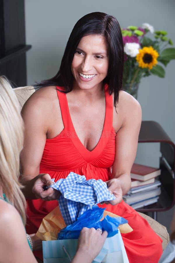 Mulher gravida com roupa do bebê imagens de stock