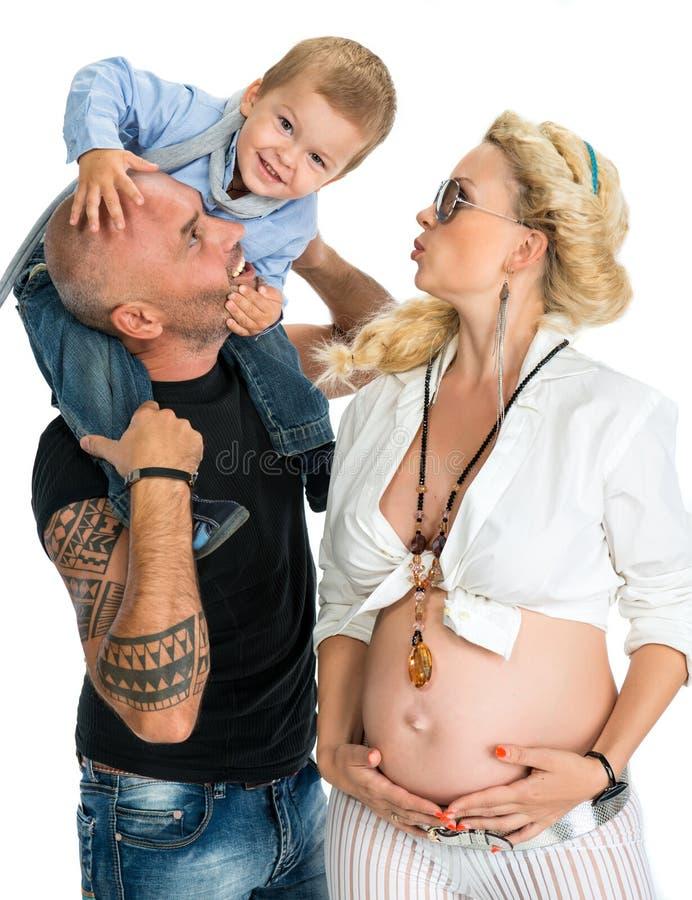 Mulher gravida com seu marido e seu filho que beijam sua barriga imagens de stock royalty free
