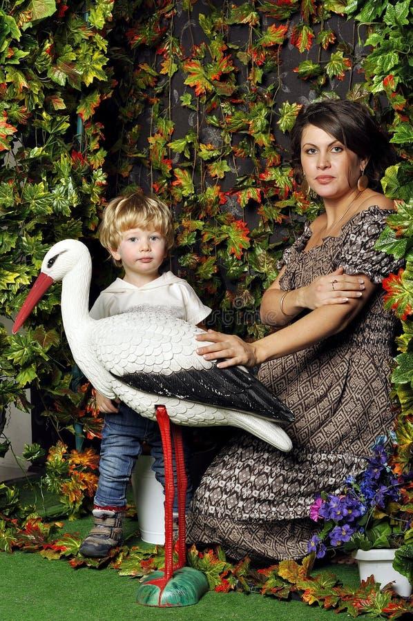 Mulher gravida com sua criança no jardim que olha a cegonha do toque do estilo do estúdio fotografia de stock