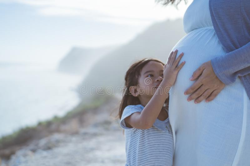 Mulher gravida com sua filha bonito pequena na praia fotografia de stock royalty free