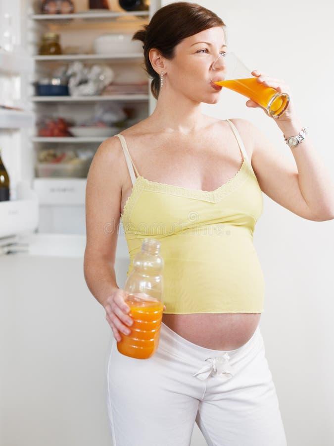 Mulher gravida com suco imagem de stock royalty free