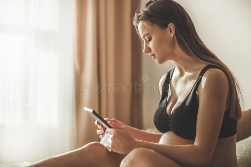 Mulher gravida com a tabuleta moderna que senta-se na cama e que ajusta seu cabelo longo Conceito da gravidez e da tecnologia foto de stock