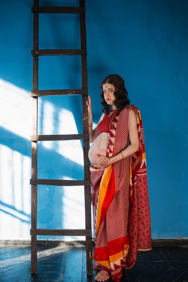 A mulher gravida com tatuagem da hena fotografia de stock royalty free