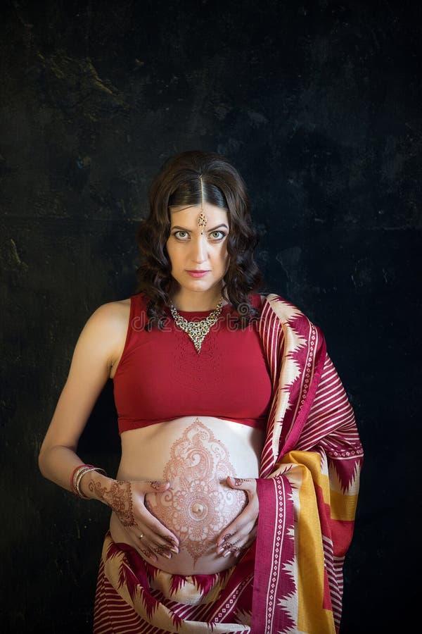 A mulher gravida com tatuagem da hena fotografia de stock
