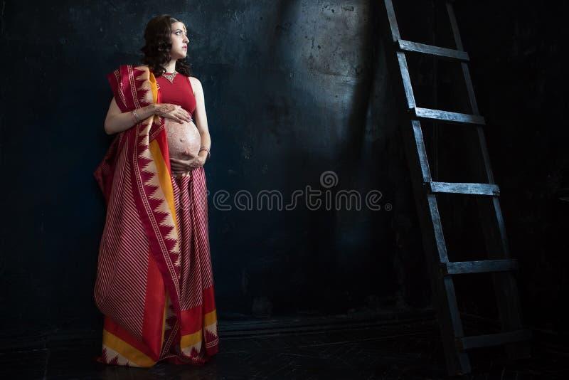 A mulher gravida com tatuagem da hena foto de stock