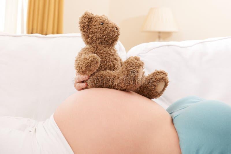 Mulher gravida com Teddy Bear Resting On Belly fotografia de stock royalty free
