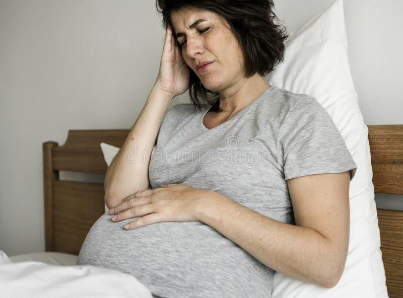 mulher gravida com uma dor de cabeça imagem de stock