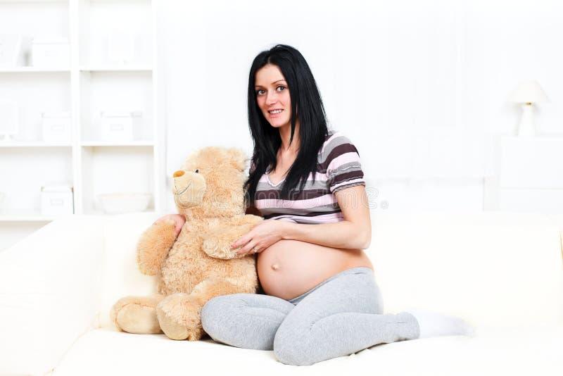 Mulher gravida com urso de peluche fotografia de stock
