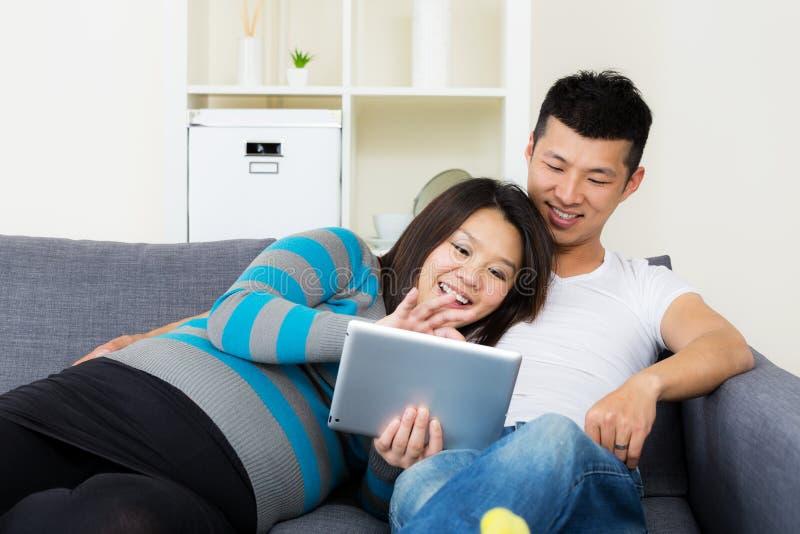 Mulher gravida de Ásia com seu marido que usa a tabuleta em casa imagem de stock