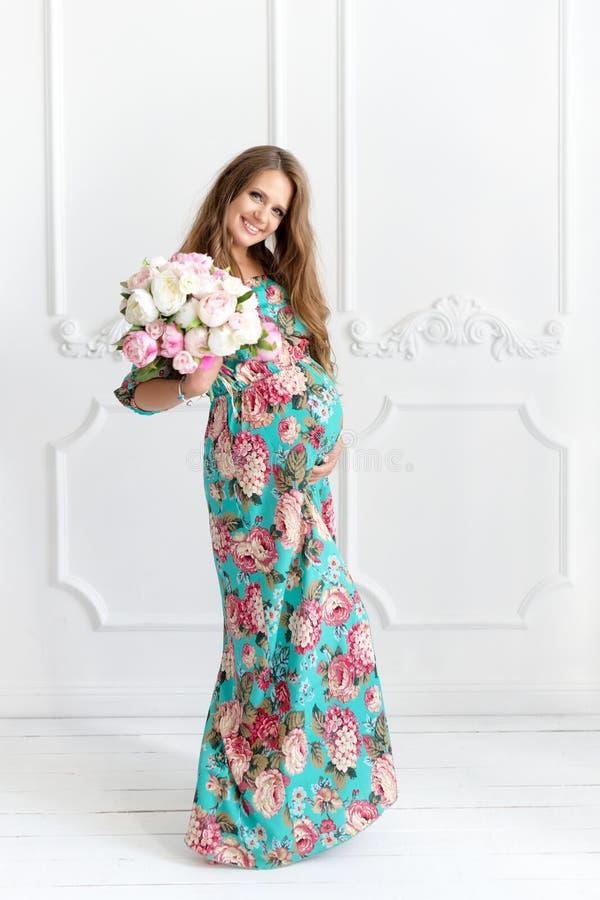 Mulher gravida de cabelos compridos feliz no ramalhete guardando interior minimalistic branco das flores imagens de stock royalty free
