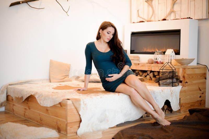 Mulher gravida de cabelos compridos nova e bonita que senta-se perto da chaminé foto de stock