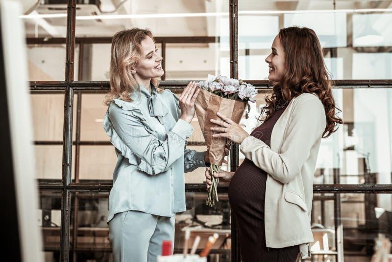 Mulher gravida de cabelos compridos de sorriso que recebe o ramalhete do colega de irradiação imagem de stock royalty free