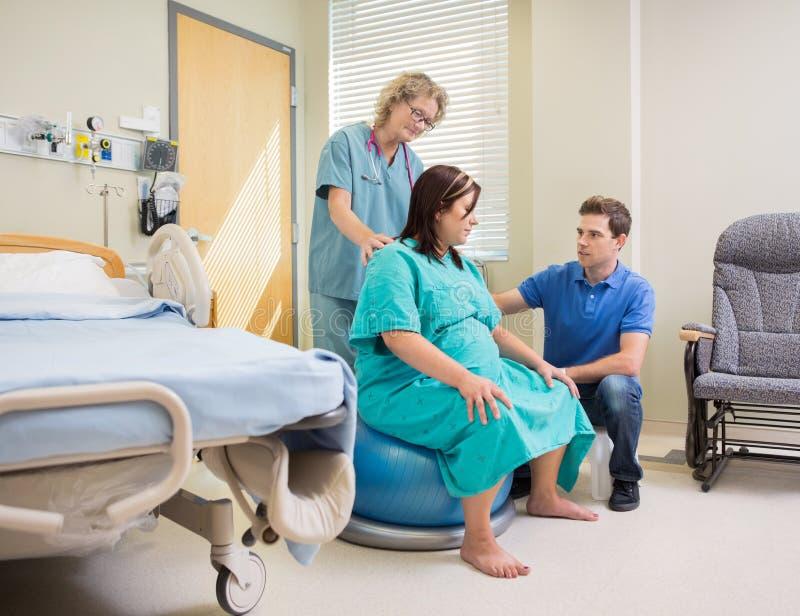 Mulher gravida de And Man Assisting da enfermeira no exercício imagem de stock royalty free