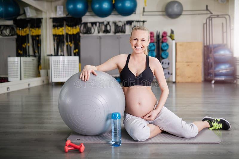 Mulher gravida de riso que senta-se no gym com bola dos pilates fotografia de stock royalty free
