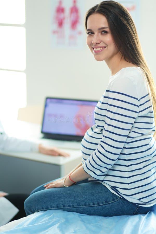 Mulher gravida de sorriso bonita com o doutor no hospital imagem de stock royalty free